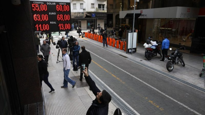 A man takes a photo of the exchange rate displayed on a currency exchange board in Buenos Aires.